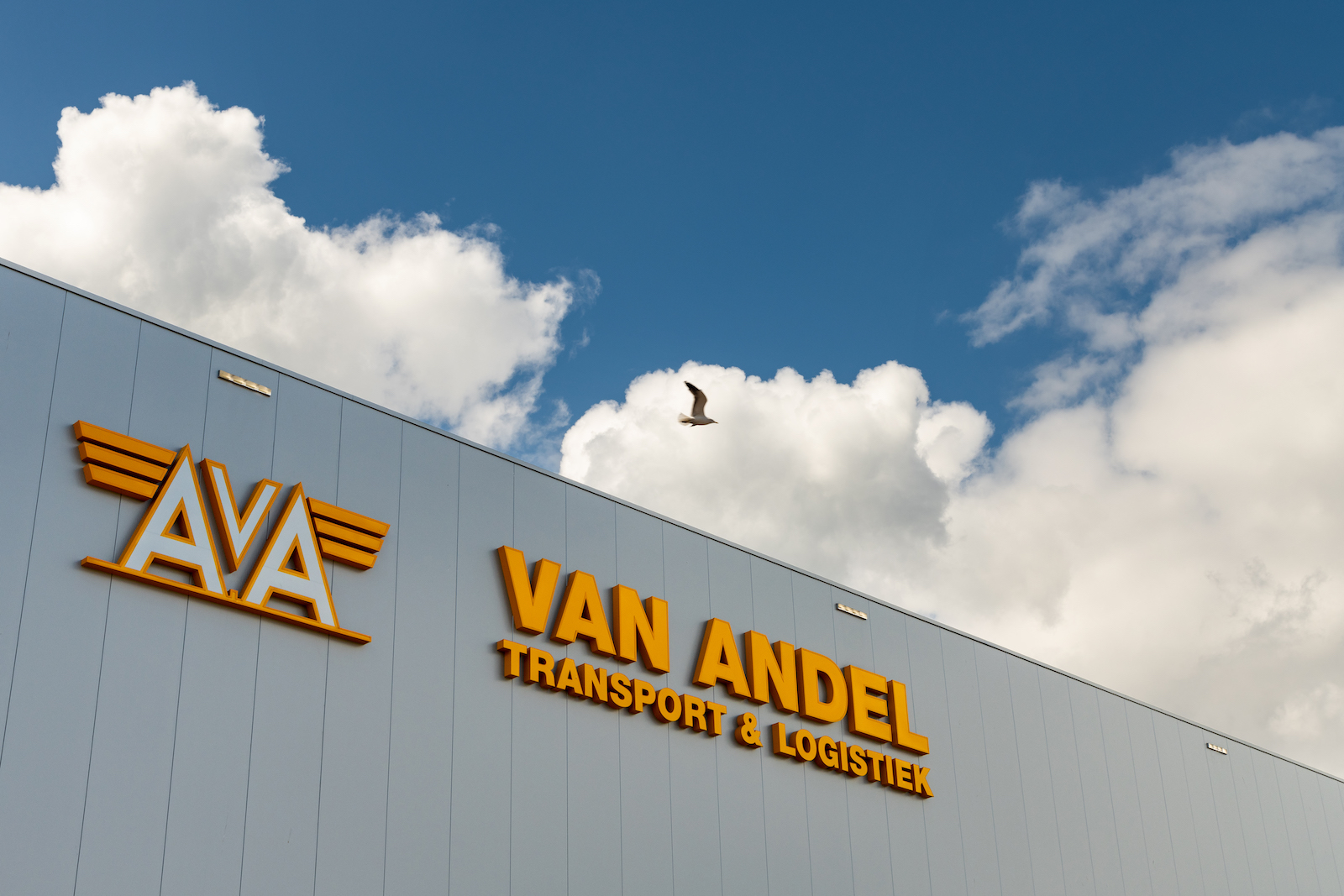 Korteland In- en Outdoor Signing Van Andel gele lichtgevende letters op grijs gebouw blauwe licht wolken